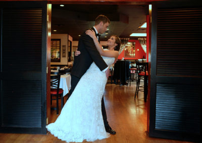 A groom dipping his bride during their wedding reception in Rococo Northpark's Private Dining Room